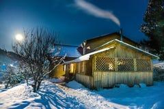 Maison en bois dans la neige la nuit hiver Image libre de droits