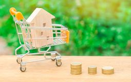 Maison en bois dans un chariot à supermarché Investissement de propriété et concept financier d'hypothèque de maison achat, locat Images libres de droits