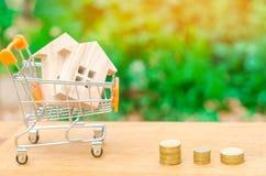 Maison en bois dans un chariot à supermarché Investissement de propriété et concept financier d'hypothèque de maison achat, locat Photographie stock