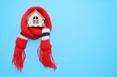 Maison en bois de jouet avec des fenêtres dans une écharpe rouge sur un fond bleu, maison chaude, isolation de maison, copyspace photographie stock