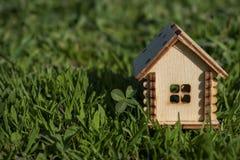 Maison en bois de jouet sur l'herbe lumineuse par temps ensoleillé Copiez l'espace Concept d'immobiliers, concept de financement  image stock