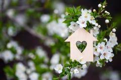 Maison en bois de plan rapproch? avec le trou sous la forme de coeur entour?e par les branches fleurissantes blanches des arbres  photographie stock libre de droits