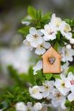 Maison en bois de plan rapproch? avec le trou sous la forme de coeur entour?e par les branches fleurissantes blanches des arbres  photos stock