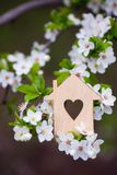 Maison en bois de plan rapproch? avec le trou sous la forme de coeur entour?e par les branches fleurissantes blanches des arbres  images stock