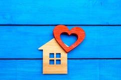 Maison en bois et coeur rouge sur un fond en bois bleu Photo stock
