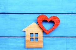 Maison en bois et coeur rouge sur un fond en bois bleu Concept de l'amour Photos stock