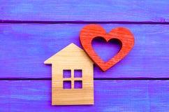 Maison en bois et coeur rouge sur un fond en bois pourpre Photographie stock