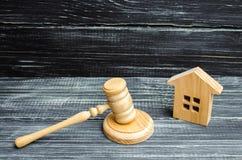 Maison en bois et un marteau du juge sur un fond noir Affaires en jugement sur la propriété et les immobiliers Confiscation et na Image libre de droits