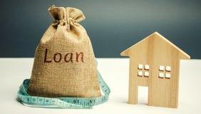 Maison en bois et un sac avec le prêt de mot et un ruban métrique Achat d'une maison dans la dette Investissement immobilier de f images libres de droits