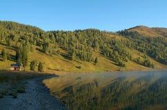 Maison en bois isolée dans les montagnes près du lac Images libres de droits
