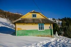 Maison en bois neigeuse de vieux cru Jour ensoleillé d'hiver Montagnes et forêt photos stock