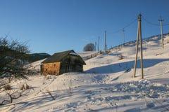 Maison en bois neigeuse de vieux cru Jour ensoleillé d'hiver Montagnes et forêt photo libre de droits