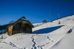 Maison en bois neigeuse de vieux cru Jour ensoleillé d'hiver Montagnes et forêt image libre de droits