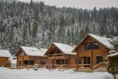 Maison en bois neigeuse de vieux cru L'hiver Montagnes et forêt image stock