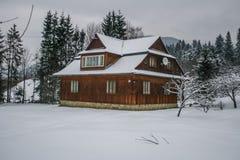 Maison en bois neigeuse de vieux cru L'hiver Montagnes et forêt photo stock