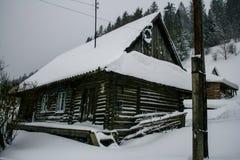 Maison en bois neigeuse de vieux cru L'hiver Montagnes et forêt photographie stock