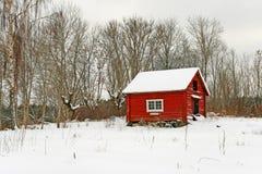 Maison en bois rouge suédoise traditionnelle dans la neige Photo stock