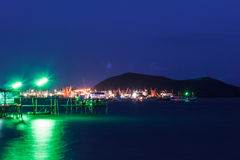 Maison en bois sur la mer la nuit avec la lumière de couleur Image libre de droits
