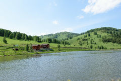 Maison en bois sur le rivage d'un lac de montagne un été ensoleillé d Image stock