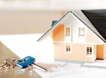 Maison et clé miniatures sur le modèle Image stock