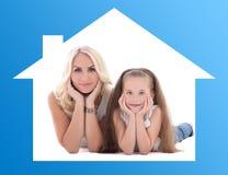 Maison et concept de la famille - mère avec son petit mensonge de fille Photos libres de droits