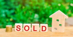Maison et pièces de monnaie en bois avec le ` vendu par ` d'inscription vente de propriété, maison, immobiliers Boîtier accessibl Image libre de droits