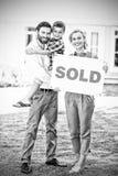 Maison extérieure debout de famille avec le signe vendu photos stock