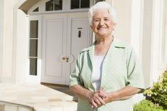 Maison extérieure debout de femme aîné Photographie stock libre de droits