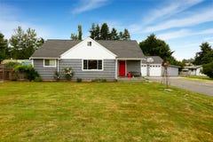 Maison grise avec l'équilibre blanc et la porte rouge photos stock