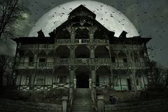 Maison hantée rampante avec l'atmosphère foncée d'horreur Un chat noir, beaucoup de battes et grande pleine lune dans la coulisse photographie stock