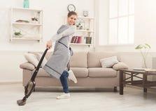 Maison heureuse de nettoyage de femme avec l'aspirateur photo libre de droits