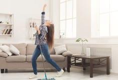 Maison heureuse de nettoyage de femme avec le balai et l'amusement de avoir photographie stock libre de droits