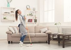 Maison heureuse de nettoyage de femme avec le balai et l'amusement de avoir photo stock