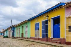 Maison jaune avec la porte bleue et fenêtres au Trinidad, Cuba Photo stock