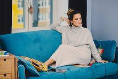 Maison, loisirs et concept de bonheur - adolescente de sourire se trouvant sur le sofa images stock