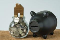 maison miniature sur la bouteille en verre de pot avec complètement de pièces de monnaie et de blac photos libres de droits