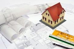 Maison modèle sur un plan de construction images stock