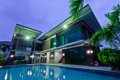 Maison moderne avec la piscine la nuit Photographie stock libre de droits