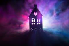 Maison noire avec un coeur et ciel brumeux modifié la tonalité à l'arrière-plan Approprié aux concepts tels que la maison d'amour Images libres de droits