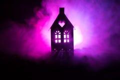 Maison noire avec un coeur et ciel brumeux modifié la tonalité à l'arrière-plan Approprié aux concepts tels que la maison d'amour Photographie stock