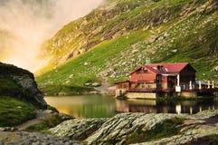 Maison rêveuse de lac dans les montagnes Photos libres de droits