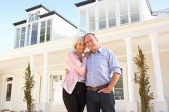 Maison rêveuse extérieure debout de couples aînés Photo stock