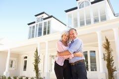 Maison rêveuse extérieure debout de couples aînés Photo libre de droits