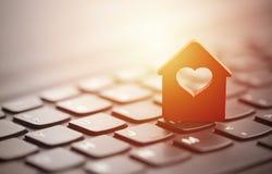 Maison rouge avec le coeur au-dessus du clavier d'ordinateur portable Photos stock