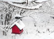 Maison rouge d'oiseau couverte de neige Photos stock