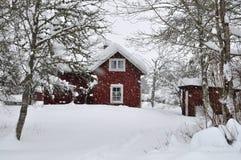 Maison rouge en chutes de neige Photos libres de droits