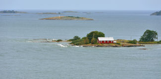 Maison rouge isolée sur le rivage rocheux de la mer baltique Photo libre de droits