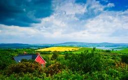 Maison rouge sous le ciel excessif, Irlande Photo libre de droits