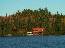 Maison rouge sur le rivage de lac Photographie stock