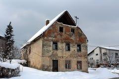 Maison ruinée abandonnée avec les fenêtres cassées et les briques tombées couvertes dans la neige Photographie stock libre de droits